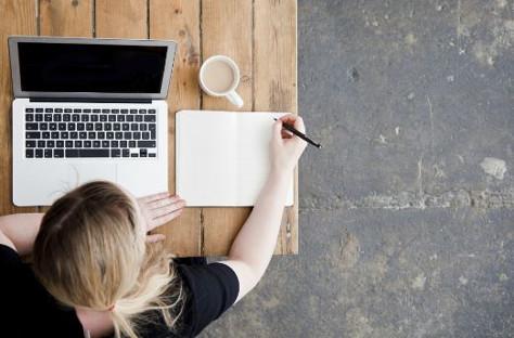 Blonde woman writing engaging Facebook Ads